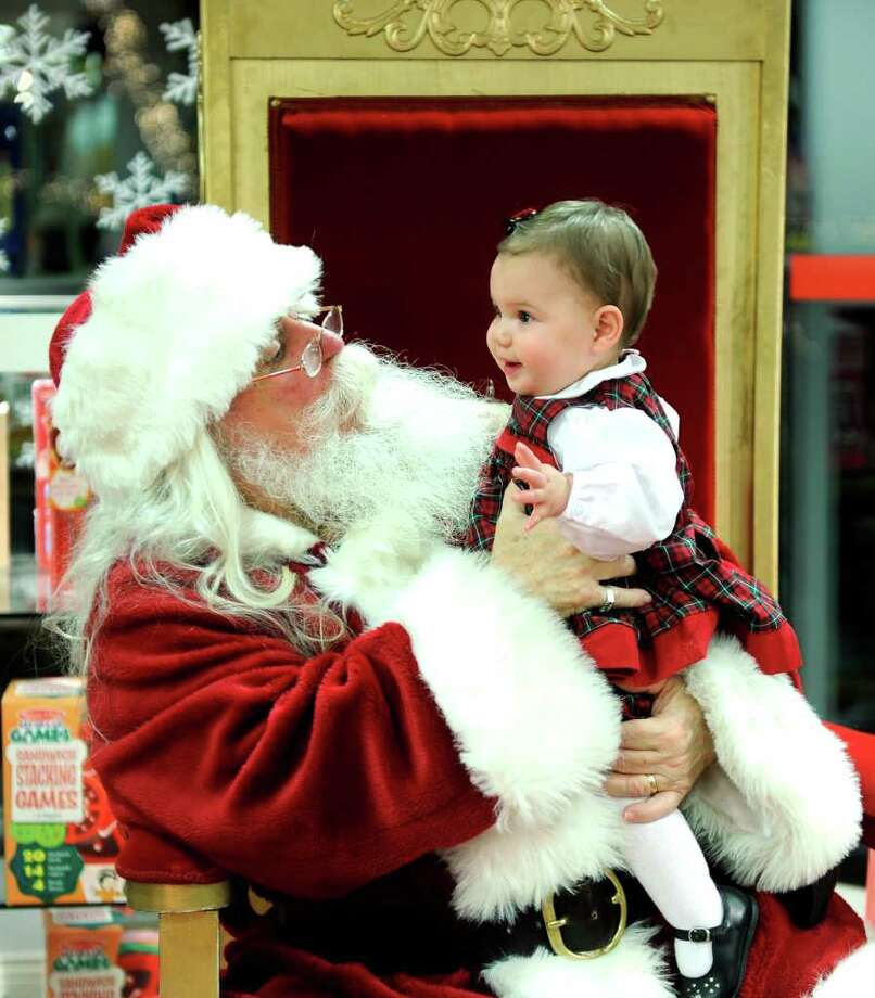 Santa Claus, aka Joe Warren, talks to nine-month-old Callie Wilson, of Stamford, Thursday, December 22, 2011 at the Darien Sports Shop.  Warren has been appearing at the shop in Darien, free of charge, for 33 years. Photo: Autumn Driscoll / Connecticut Post
