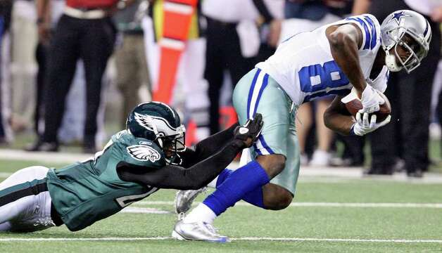 Dallas Cowboys' Dez Bryant tries to shake the tackle of Philadelphia Eagles' Brandon Hughes during first half action Saturday Dec. 24, 2011 at Cowboys Stadium in Arlington, TX. PHOTO BY EDWARD A. ORNELAS/eaornelas@express-news.net) Photo: EDWARD A. ORNELAS, Express-News / © SAN ANTONIO EXPRESS-NEWS (NFS)