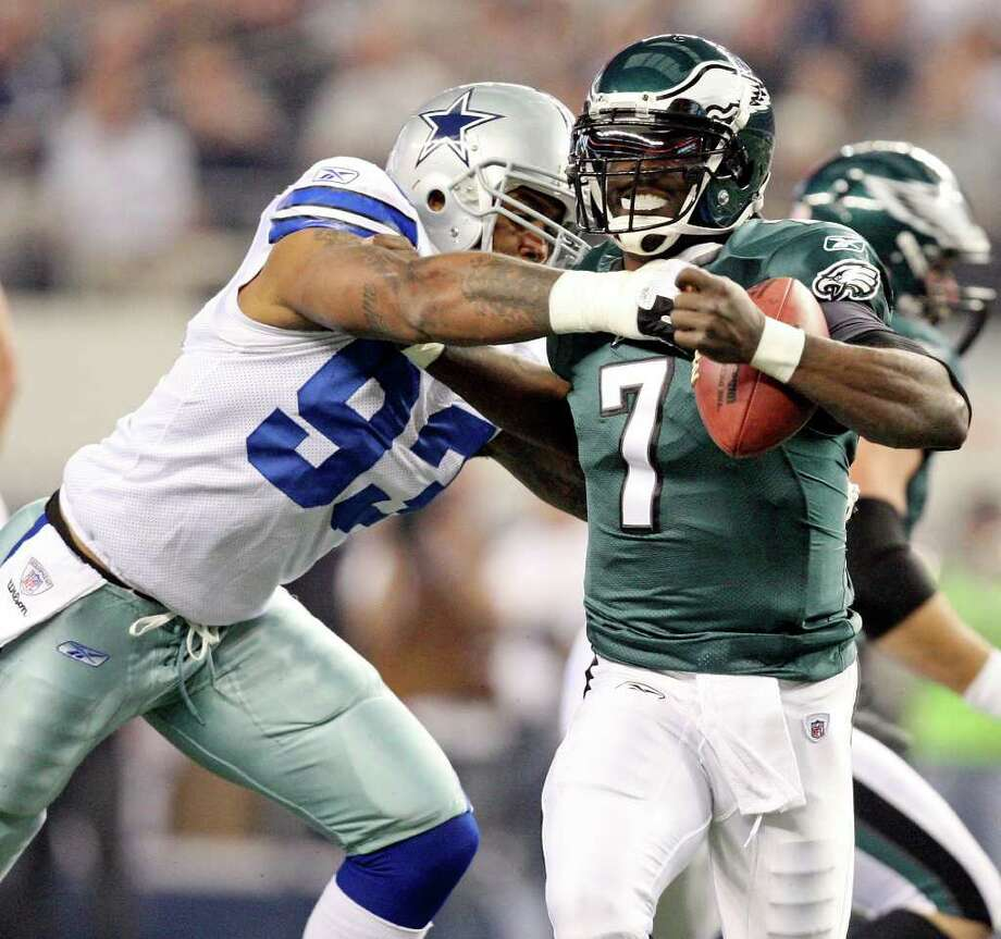 Philadelphia Eagles' Michael Vick looks for room around Dallas Cowboys' Anthony Spencer during first half action Saturday Dec. 24, 2011 at Cowboys Stadium in Arlington, TX. Spencer was called for a face mask on the play. PHOTO BY EDWARD A. ORNELAS/eaornelas@express-news.net) Photo: EDWARD A. ORNELAS, Express-News / © SAN ANTONIO EXPRESS-NEWS (NFS)