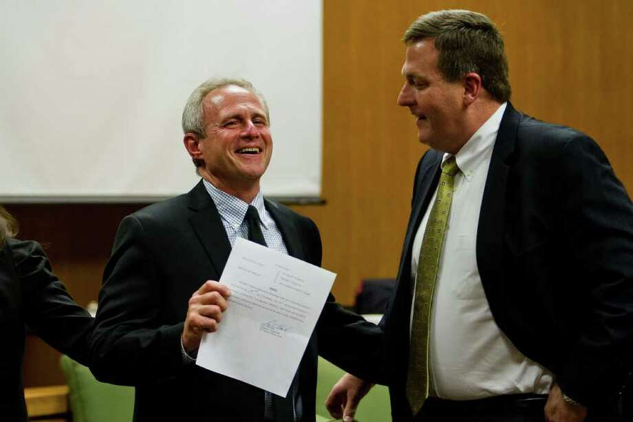 CALLIE RICHMOND : FOR THE CHRONICLE FREE MAN: Michael Morton holds the order officially clearing him of murder in a packed Williamson County courtroom on Monday as his attorney, John Raley, shares Morton's joy. Photo: Callie Richmond / Callie Richmond