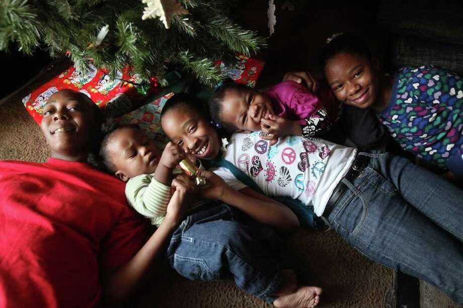 LaTonya Williams, 38, son Tony McFarland, 11 months, daughters Alexus Cormier, 10, Mya McFarland, 2 years-old, and Diamond Cormier, 11, are photographed by their Christmas presents and are recipients of the Houston Chronicle's Goodfellows Program on Saturday, Dec. 24, 2011, in Houston. Photo: Mayra Beltran, Houston Chronicle / © 2011 Houston Chronicle