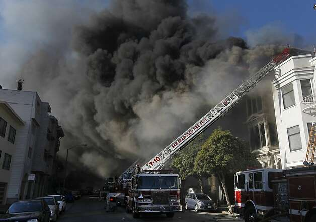 Golden Gate Avenue is darkened by a five-alarm fire that left about 60 people homeless. Only two injuries were reported. Photo: Paul Chinn, The Chronicle