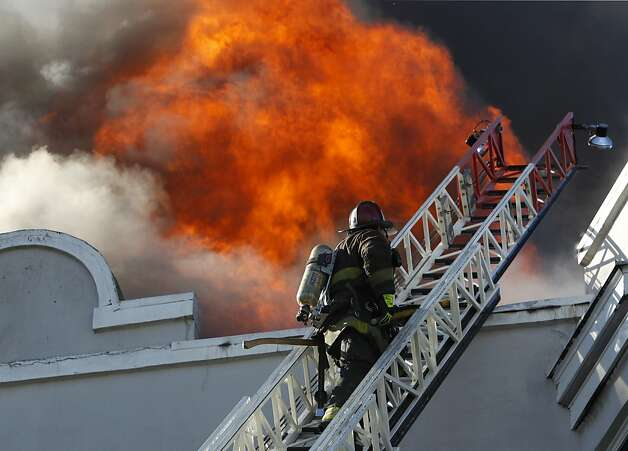 A firefighter nears the roof of a building engulfed by a five-alarm fire at Pierce Street and Golden Gate Avenue in San Francisco, Calif. on Thursday, Dec. 22, 2011. Photo: Paul Chinn, The Chronicle