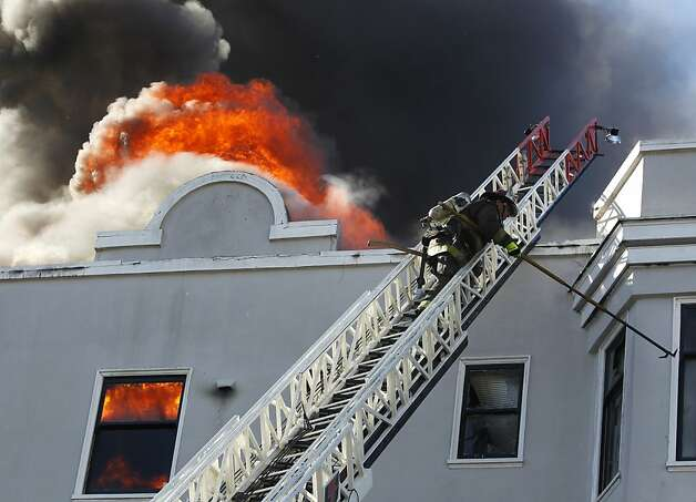 A firefighter smashes windows to ventilate a five-alarm fire at Pierce Street and Golden Gate Avenue in San Francisco, Calif. on Thursday, Dec. 22, 2011. Photo: Paul Chinn, The Chronicle
