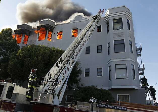 San Francisco firefighters battle a fire that began in an apartment building at Golden Gate Avenue and Pierce Street in the Western Addition before spreading to an adjacent building. Photo: Paul Chinn, The Chronicle