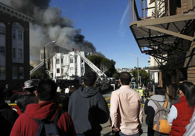 Neighbors watch firefighters battle a five-alarm fire at Pierce Street and Golden Gate Avenue in San Francisco, Calif. on Thursday, Dec. 22, 2011. Photo: Paul Chinn, The Chronicle
