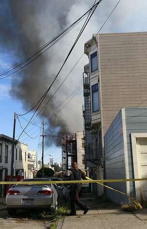 A San Francisco police officer puts police tape up near an apartment fire in the Western Addition area of San Francisco, Thursday, Dec. 22, 2011. (AP Photo/Jeff Chiu) Photo: Jeff Chiu, Associated Press