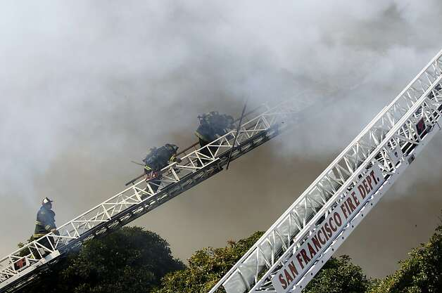 Firefighters retreat from the roof while battling a five-alarm fire at Pierce Street and Golden Gate Avenue in San Francisco, Calif. on Thursday, Dec. 22, 2011. Photo: Paul Chinn, The Chronicle