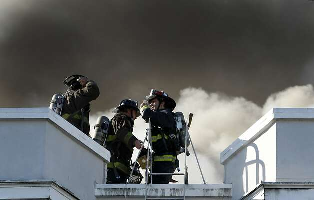 Firefighters work on the roof of an apartment building involved in a five-alarm fire at Pierce Street and Golden Gate Avenue in San Francisco, Calif. on Thursday, Dec. 22, 2011. Photo: Paul Chinn, The Chronicle