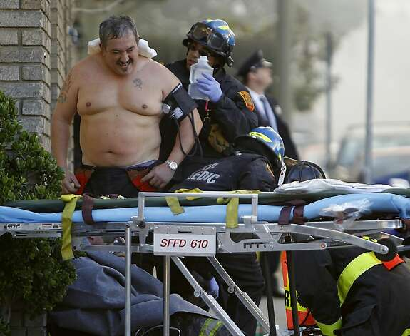An unidentified firefighter, one of scores who responded, is treated at the scene of the fire in the Western Addition. Photo: Paul Chinn, The Chronicle