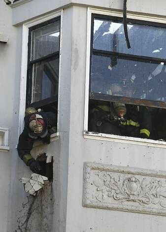 Firefighters mop up after extinguishing a five-alarm fire at Pierce Street and Golden Gate Avenue in San Francisco, Calif. on Thursday, Dec. 22, 2011. Photo: Paul Chinn, The Chronicle