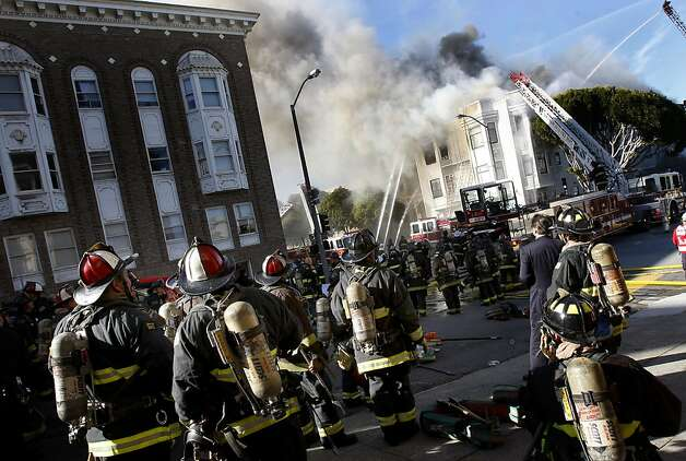 Dozens of firemen, held in reserve, watched the fire burn from Pierce Street. A five alarm fire near the corner of Pierce and Golden Gate Avenues in San Francisco, Calif.  demolished three buildings and displaced dozens, but early on there were only reports of minor injuries Thursday December 22, 2011. Photo: Brant Ward, The Chronicle