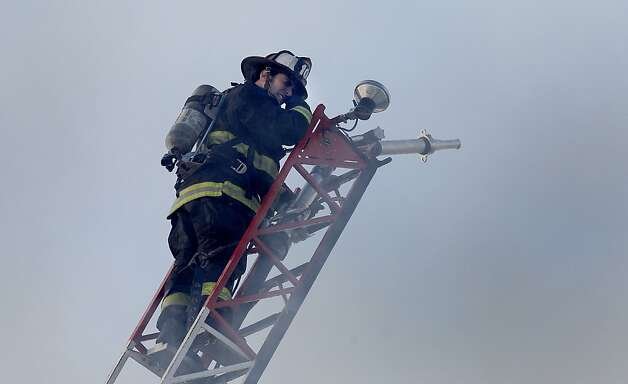 A fireman wiped his eyes from all the smoke as he climbed a ladder truck. A five alarm fire near the corner of Pierce and Golden Gate Avenues in San Francisco, Calif.  demolished three buildings and displaced dozens, but early on there were only reports of minor injuries Thursday December 22, 2011. Photo: Brant Ward, The Chronicle