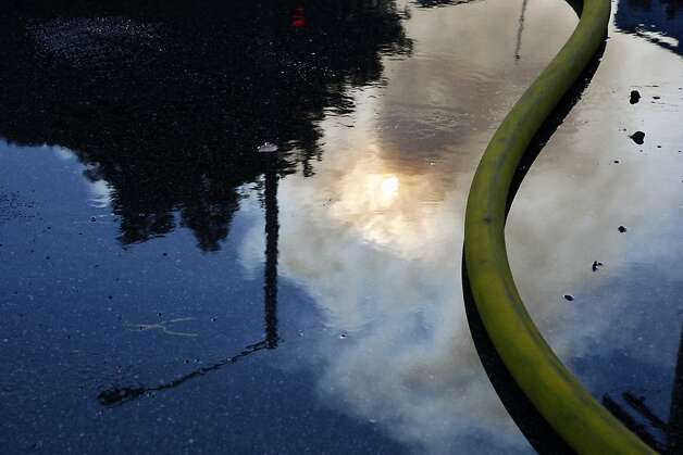 A reflection of smoke can be seen in firefighter's water pooling in the intersection of Pierce Street and Turk Street on Thursday, December 22, 2011 in San Francisco, Calif. Photo: Beck Diefenbach, Special To The Chronicle