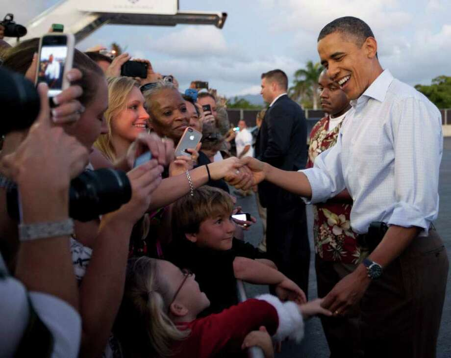 President Barack Obama shakes hands with people waiting to greet him on the tarmac as he steps off of Air Force One at Hickam Air Force Base in Friday, Dec. 23, 2011, in Honolulu. (AP Photo/Carolyn Kaster) Photo: Carolyn Kaster / AP
