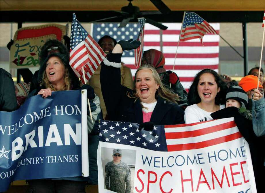 From left, Janine Halverson, Shelly Hamedi and Kristiana Deweese cheer as the U.S. Army 1st Cavalry 3rd Brigade soldiers arrive at Fort Hood, Texas, Saturday, Dec. 24, 2011, returning home from deployment in Iraq. The ladies were greeting Spc. Brian Hamedi, who is Hamedi's son and Deweese's fiance. These 3rd Brigade troops were in the last convoy to leave Iraq as U.S. troops ended their stay. (AP Photo/Erich Schlegel) Photo: Erich Schlegel