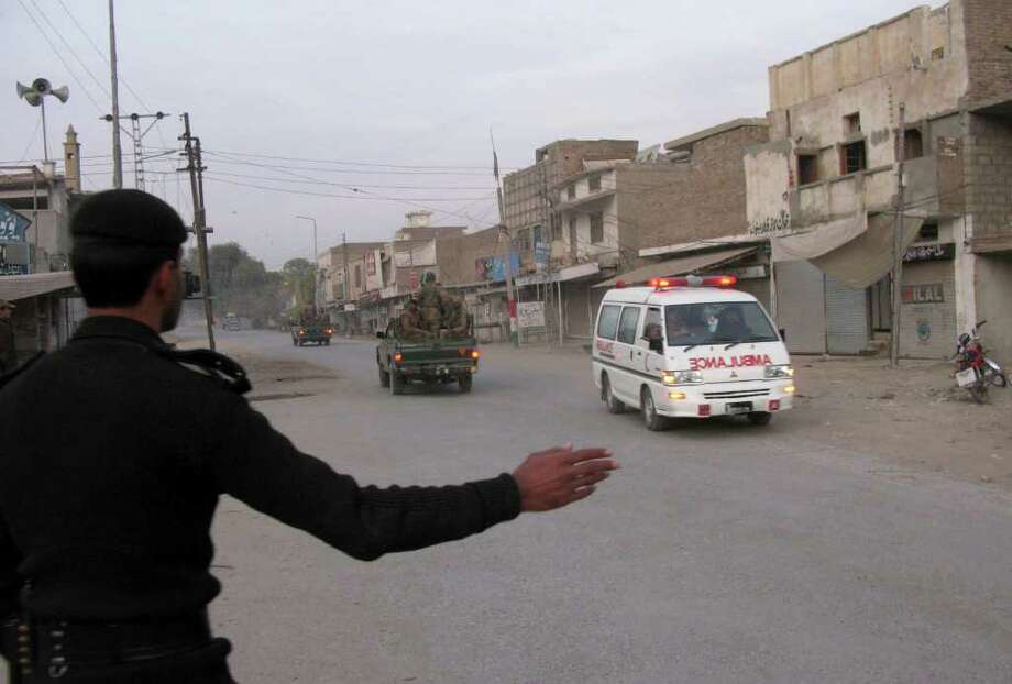 A Pakistani police officer, left, makes a way to an ambulance rushing to the site of a blast at a paramilitary camp in Bannu, Pakistan, Saturday, Dec. 24, 2011. A Pakistani Taliban suicide bomber rammed a car filled with explosives into the paramilitary camp in northwestern Pakistan on Saturday, killing six soldiers in the second attack in as many days meant to avenge the killing of senior commander in a U.S. drone strike. (AP Photo/Ijaz Muhammad) Photo: Ijaz Muhammad