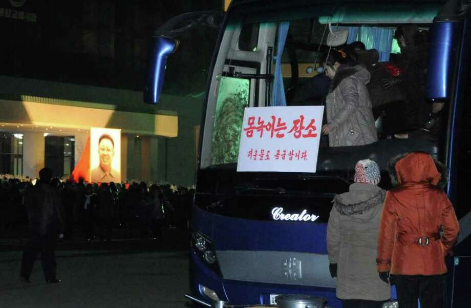 """Mourners use a bus to stay warm as many gather around a portrait of the late leader Kim Jong Il hanging outside the Pyongyang Circus Theater in Pyongyang, North Korea on Saturday, Dec. 24, 2011. The sign on the bus window reads """"Warm rest area. Warm water also available"""". North Korea on Saturday called Kim Jong Il's son """"supreme leader"""" of the military, dramatically ramping up its campaign to install the young man as next leader even as millions continued mourning the father. (AP Photo)"""