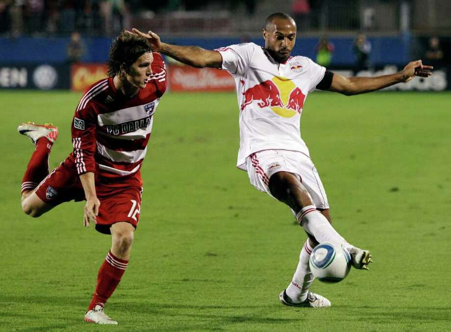 FILE - In this Oct. 26, 2011, file photo, New York Red Bulls forward Thierry Henry, right, makes a pass to center as FC Dallas defender Zach Loyd, left, pursues in the second half of an MLS Cup soccer match in Frisco, Texas. Arsenal manager Arsene Wenger is considering trying to bring Henry back to the club on a two-month loan from the Red Bulls to fill the void left by strikers going to the African Cup of Nations. (AP Photo/Tony Gutierrez, File) Photo: Tony Gutierrez