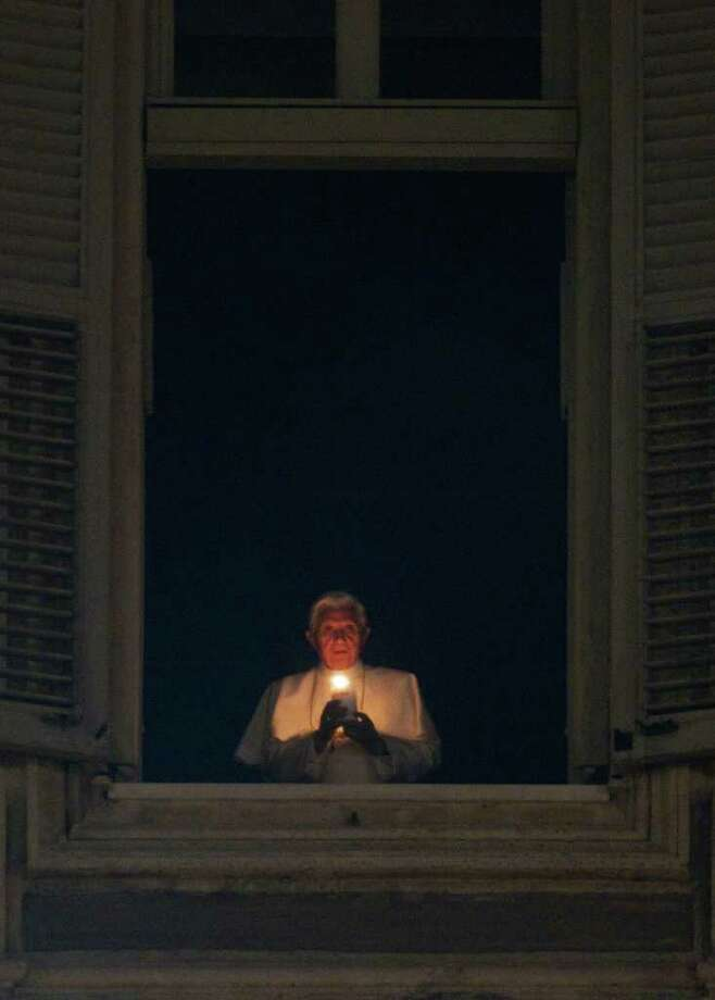Pope Benedict XVI lights a candle at his studio window overlooking St. Peter's Square at the Vatican, Saturday, Dec. 24, 2011. Pope Benedict XVI celebrates Christmas Eve Mass on Saturday night, kicking off a busy two weeks of public appearances that will test his stamina. Hours before the evening Mass began, Benedict lit a candle in his studio window overlooking St. Peter's Square in a traditional sign of peace. (AP Photo/Andrew Medichini) Photo: Andrew Medichini / AP