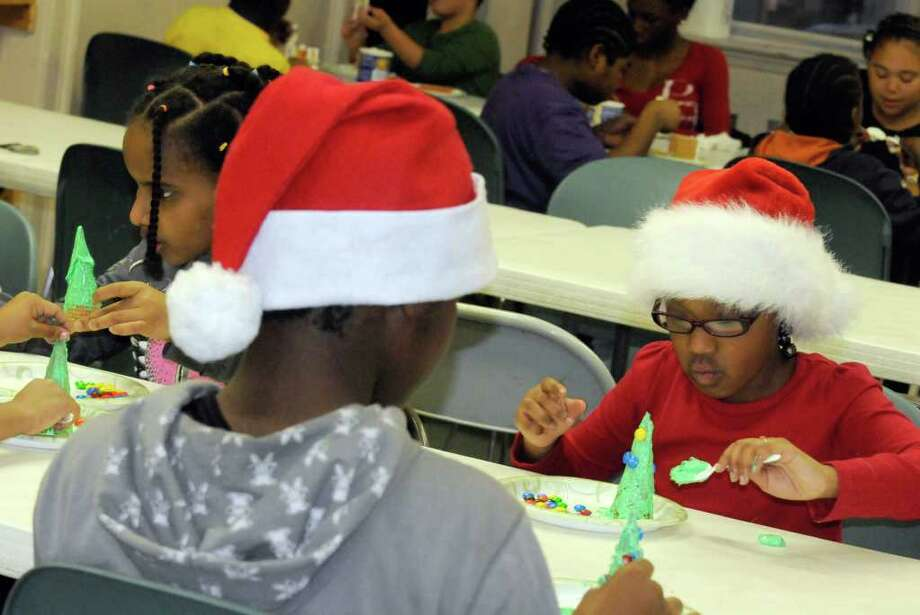 Eight-year-old Alyrah Pettiway,right, of Albany works on her candy Christmas tree during the trinity Alliance of the Capital Region after school program in Albany, NY Friday, Dec.23, 2011.( Michael P. Farrell/Times Union) Photo: Michael P. Farrell