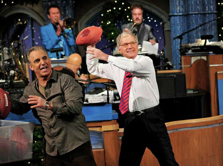 """In this photo released by CBS, host David Letterman, right, and comic Jay Thomas get ready to throw footballs at the Late Show Christmas tree during the annual Late Show Holiday Quarterback Challenge on the set of """"Late Show with David Letterman,"""" airing Thursday, Dec. 23, 2011 on the CBS Television Network.  Thomas and Letterman each take turns tossing footballs at the Late Show Christmas tree to try and knock off the giant meatball perched at its top.   (AP Photo/CBS, John Paul Filo) Photo: John Paul Filo"""