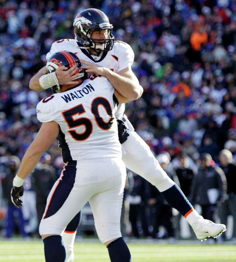 Denver Broncos' Tim Tebow (15) celebrates his touchdown with teammate J. D. Walton (50)  during the first quarter of an NFL football game against the Buffalo Bills in Orchard Park, N.Y., Saturday, Dec. 24, 2011. (AP Photo/David Duprey) Photo: David Duprey