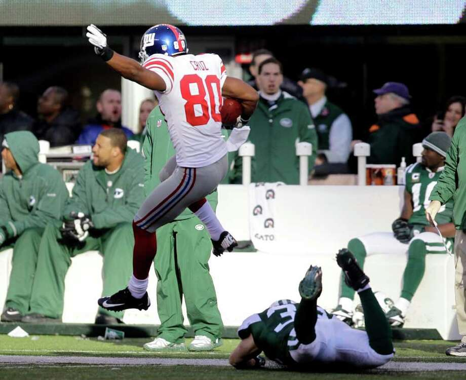 New York Giants' Victor Cruz jumps over a New York Jets defender while scoring 99-yard touchdown during the second quarter of an NFL football game Saturday, Dec. 24, 2011, in East Rutherford, N.J. (AP Photo/Julio Cortez) Photo: Julio Cortez