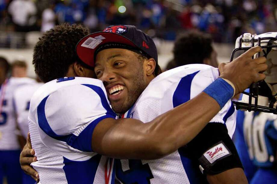 Jarrett Irving, right, is quick to show his allegiance to UH by donning a Cougars cap while celebrating a Class 5A title with Dekaney teammates. Photo: Smiley N. Pool / © 2011  Houston Chronicle