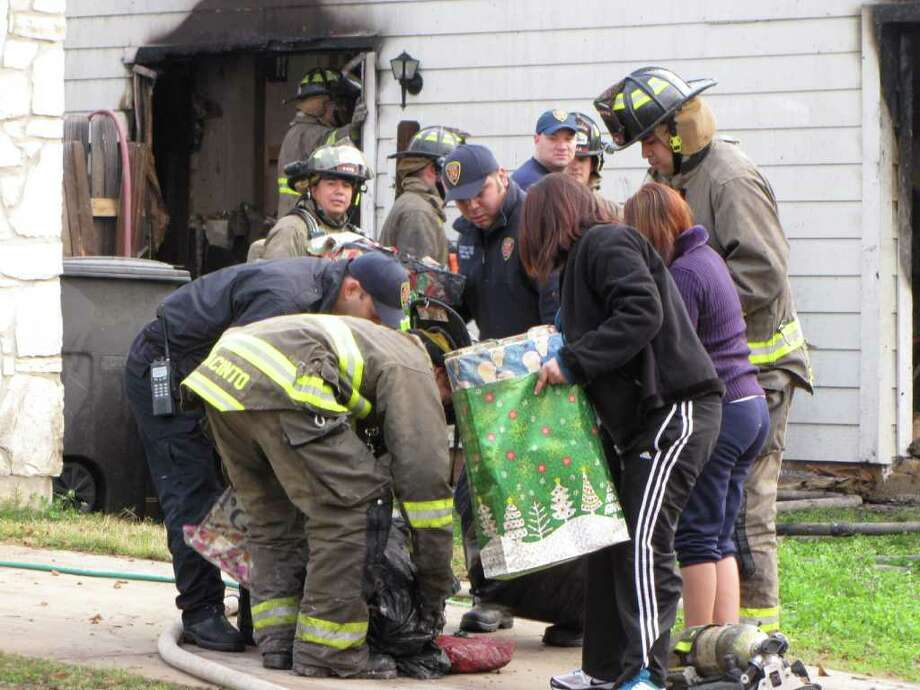 San Antonio firefighters and neighbors move a pile of presents salvaged from beneath a tree that reportedly caught on fire, destroying a Northwest Side home, early Sunday, Dec. 25, 2011. Photo: Eva Ruth Moravec/emoravec@express-news.net. / emoravec@express-news.net
