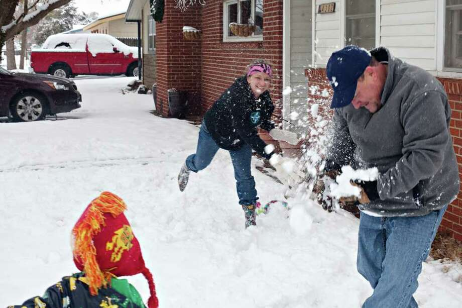 Nichole Mathis hits her husband, Mark, with a snowball as their son Jack, 4, watches during a family snowball fight Saturday, Dec. 24, 2011 outside of their home in Odessa, Texas. The National Weather service in Midland reported 3.8 inches at Midland International Airport as of 2:30 p.m. Saturday. (AP Photo/Odessa American, Albert Cesare) Photo: Albert Cesare, HC / Odessa American