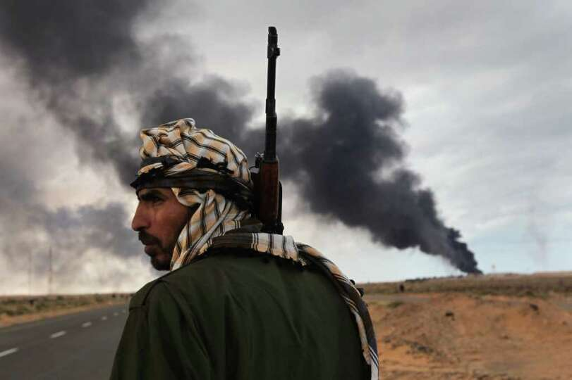 RAS LANUF, LIBYA - MARCH 09:  A Libyan rebel scans the frontline as a facility burns on the frontlin