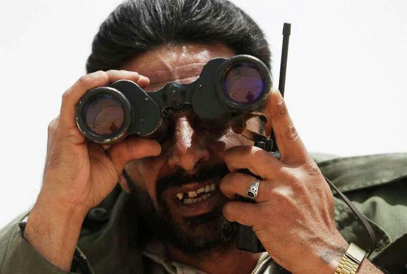 OUTSIDE BREGA, LIBYA - APRIL 06:  A Libyan rebel commander looks through binoculars as he talks on a