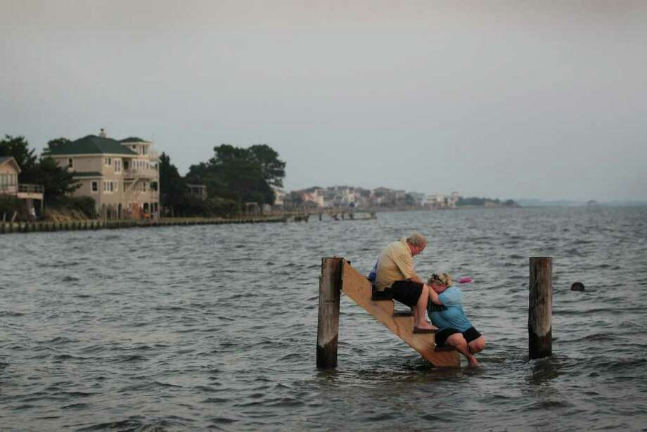 "NAGS HEAD, NC - AUGUST 28:  Billy Stinson (L) comforts his daughter Erin Stinson as they sit on the steps where their cottage once stood before it was destroyed by Hurricane Irene August 28, 2011 in Nags Head, North Carolina. The cottage, built in 1903, was one of the first vacation cottages built on Roanoke Soundin Nags Head. Stinson has owned the home, which is listed in the National Register of Historic Places, since 1963. ""We were pretending, just for a moment, that the cottage was still behind us and we were just sitting there watching the sunset,"" said Erin afterward.   (Photo by Scott Olson/Getty Images) Photo: Scott Olson, Getty Images / 2011 Getty Images"