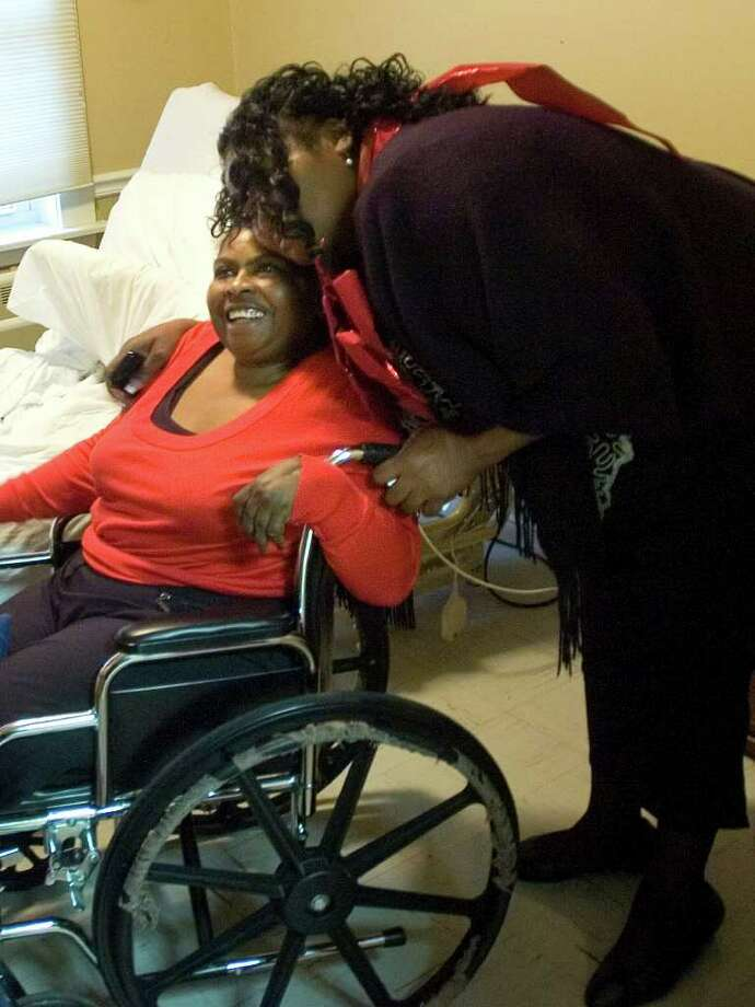 Cindy Philemon, right, hugs her sister, Delores McCray, at Glen Hill Care & Rehabilitation Center in Danbury on Sunday, Dec. 25, 2011. Philemon, who lives in Sanford, Fla., surprised her sister on Christmas morning after being apart for 34 years. Photo: Jason Rearick / The News-Times