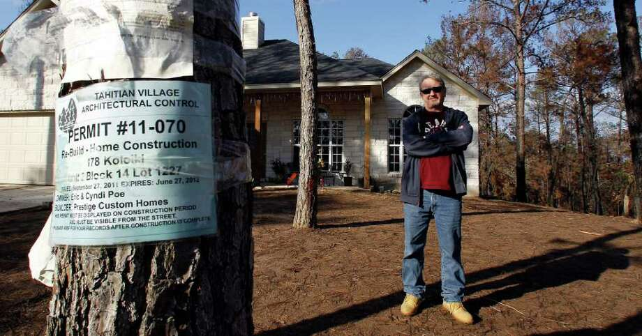 In this Dec. 6, 2011 photo, Eric Poe stands in front of his new home, in Bastrop, Texas. The Poes lost their home to a Labor Day weekend wildfire and are one of the first to rebuild. Photo: AP
