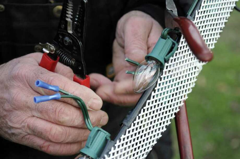 Retired electrician Bob Gauthier works on repairing a light display at the  Capital Holiday Lights display at Washington Park on Sunday, Dec. 25, 2011 in Albany, NY.   The light displays that were associated with local businesses were vandalized.  Gauthier said that whoever did the destruction, they cut individual wires between bulbs making more difficult for him to make the repairs needed to get the lights working again.   (Paul Buckowski / Times Union) Photo: Paul Buckowski