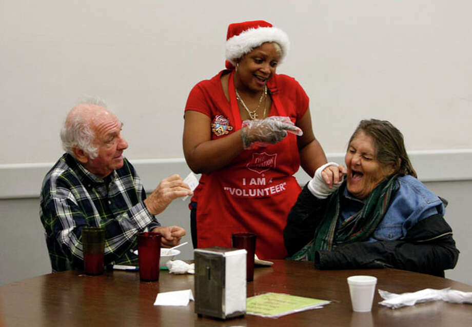 """Volunteer Pamela Palmer, center, shares a laugh with Myrtle and Luis Gerber while Palmer served Christmas day meals at the Salvation Army Harbor Light Center Sunday, Dec. 25, 2011, in Houston.  The Salvation Army Greater Houston Area served Christmas Day turkey meals to more than 500 men, women and children who did not have anywhere else to celebrate Christmas Day.   Meals were also served at the Salvation Army's Family Residence center. """"I've always wanted to volunteer, so this year I did it,"""" Palmer said. """"I love it. I love giving back and just to see happy faces I just can't explain the feeling."""" Photo: Johnny Hanson, Houston Chronicle / Houston Chronicle"""