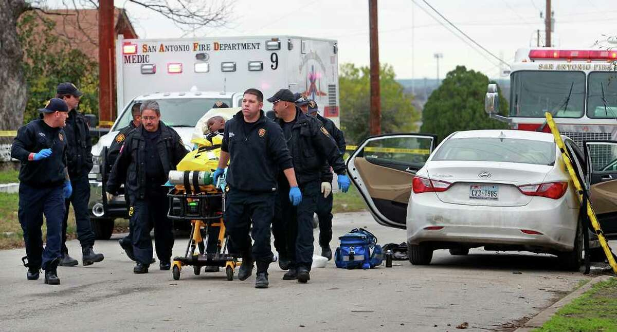 Emergency medical workers take a young boy away after treating him in the wake of a shooting on Belmont Street on Sunday, Dec. 25, 2011.