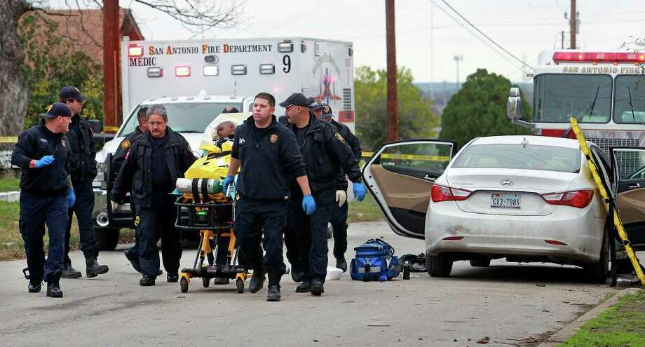 Emergency medical workers take a young boy away after treating him in the wake of a shooting on Belmont Street on Sunday, Dec. 25, 2011. Photo: TOM REEL, SAN ANTONIO EXPRESS-NEWS / © 2011 San Antonio Express-News
