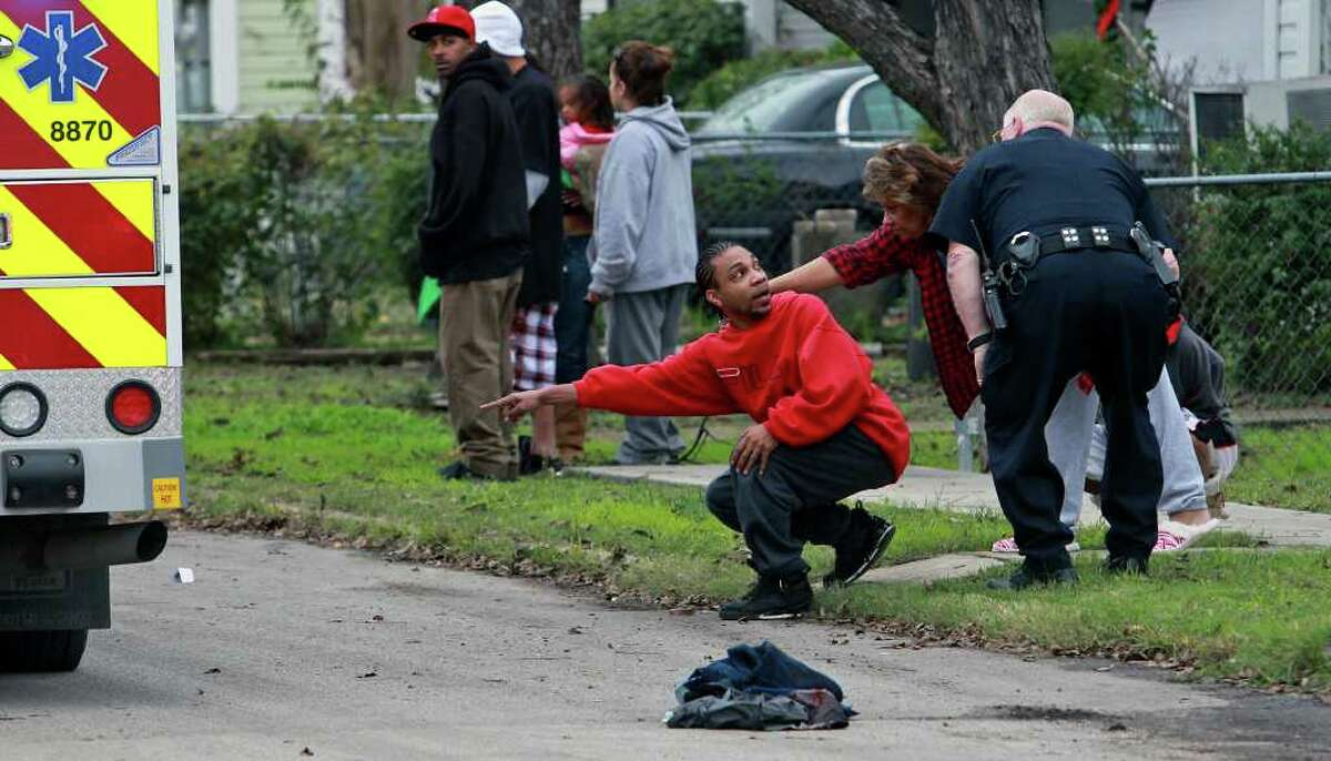 Bystanders help police locate shell casings near bloody clothing on the pavement on Belmont Street in the wake of the drive-by shooting on Sunday, Dec. 25, 2011.