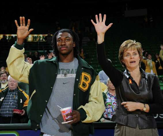 Baylor women's head basketball coach Kim Mulkey, right, and Baylor quarterback and Heisman trophy winner Robert Griffin III, left, hold up their hands  following an NCAA college basketball game between Baylor and McNeese State, Wednesday, Dec. 21, 2011, in Waco, Texas. Photo: AP