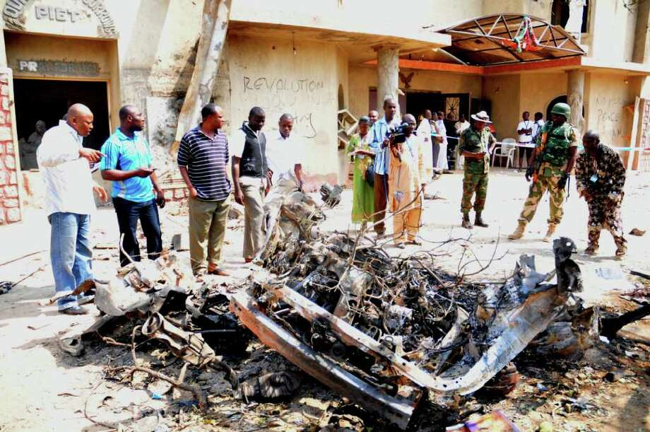 Onlookers and security staff gather around a car destroyed in a blast next to St. Theresa Catholic Church in Madalla, Nigeria, Sunday, Dec. 25, 2011. An explosion ripped through a Catholic church during Christmas Mass near Nigeria's capital Sunday, killing scores of people, officials said. A radical Muslim sect claimed the attack and another bombing near a church in the restive city of Jos, as explosions also struck the nation's northeast. (AP Photo/Dele Jones) Photo: Dele Jones / AP