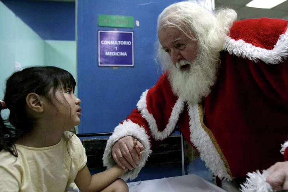Einar Sveinsson, dressed as Santa Claus, visits young patient Elizabeth Marroquin who suffers from appendicitis in the emergency room at the Benjamin Bloom Hospital in San Salvador, El Salvador, early Sunday Dec. 25, 2011. Sveinsson, who lives in El Salvador and is originally from Iceland, said he originally began volunteering in emergency rooms years ago as Santa Claus to visit children who had been burned by Christmas time firecrackers.  (AP Photo/Luis Romero) Photo: Luis Romero, Associated Press / AP