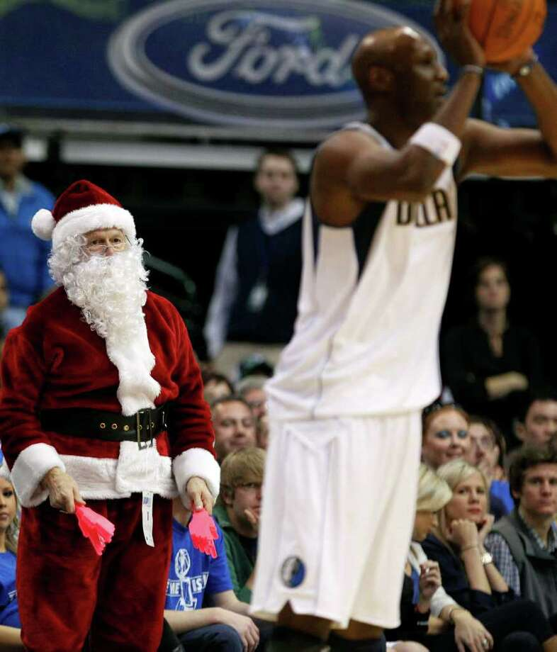Dallas Mavericks fan Don Knobler, dressed as Santa Claus, looks on as Mavericks' Lamar Odom (7) passes during an NBA basketball game against the Miami Heat in Dallas, Sunday, Dec. 25, 2011. The Mavericks lost the Christmas-day season-opener 105-94. (AP Photo/LM Otero) Photo: LM Otero, Associated Press / AP