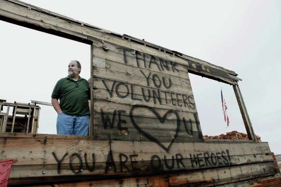 STEVE HEBERT : NEW YORK TIMES MEMORIAL: Tim Bartow ponders what's next for his damaged home, filled with messages written by volunteers, in Joplin, Mo. Officials in Joplin are discussing what to do with Bartow's home, which was filled with messages written by volunteers who flooded the community after the deadly tornado last spring. Photo: STEVE HEBERT / NYTNS