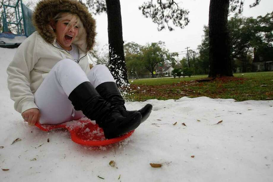 """Roxanne Carranza, 24, sleds down a ramp of snow in the front yard of her mother's home Sunday, Dec. 25, 2011, in north Houston.  Carranza's mother, Rosemary Phelan, hired a local ice making company to spray snow in her front yard so family members could celebrate a white Christmas by sledding. """"It is so fun, we had a lot more snow yesterday before the rain,"""" Roxanne Carranza said of sledding. """"Hopefully we will do it again next year."""" Photo: AP"""