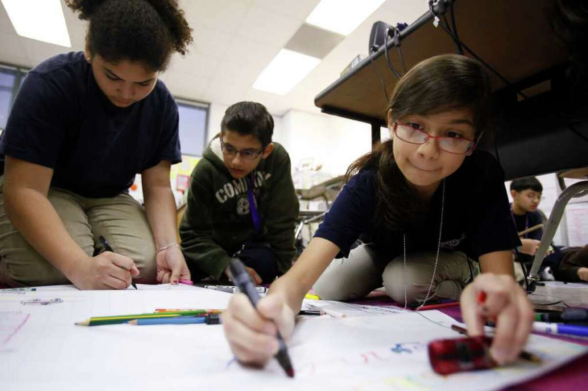 NATHAN LINDSTROM : FOR THE CHRONICLE FREEWHEELING: Jessica Flores, left, Rene Villegas and Alice Olvera work on a project in Aleah Al-Sad's seventh-grade algebra class at Stevenson Middle School. They learned to predict patterns based on the distance a hot wheel car rolled down ramps of differing heights.