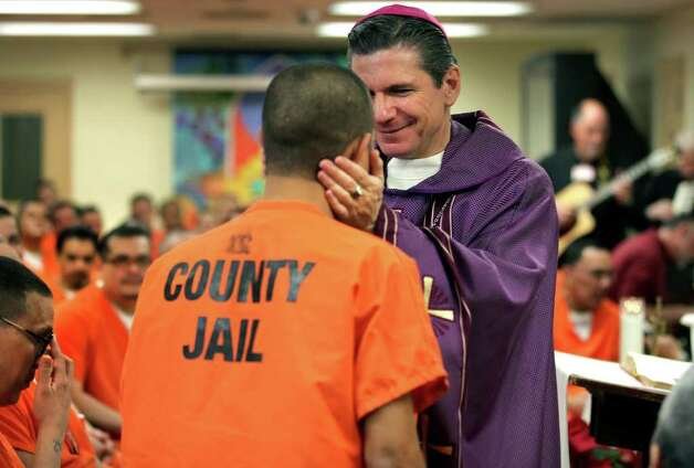 San Antonio Archbishop Gustavo Garcia-Siller blesses a Bexar County inmate after celebrating Mass inside Bexar County Jail.  Friday, Dec. 23, 2011. It was the first time in 10 years an Archbishop officiated the jail mass. Photo: BOB OWEN, SAN ANTONIO EXPRESS-NEWS / rowen@express-news.net