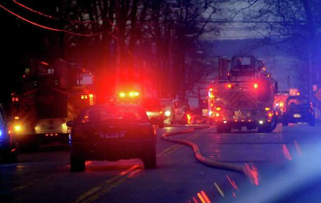 Police officers and firefighters respond to a fire on Shippan Ave. in Stamford on Christmas morning, Sunday, December 25, 2011. The fire claimed the lives of five people, including three children. Photo: Lindsay Niegelberg / Stamford Advocate